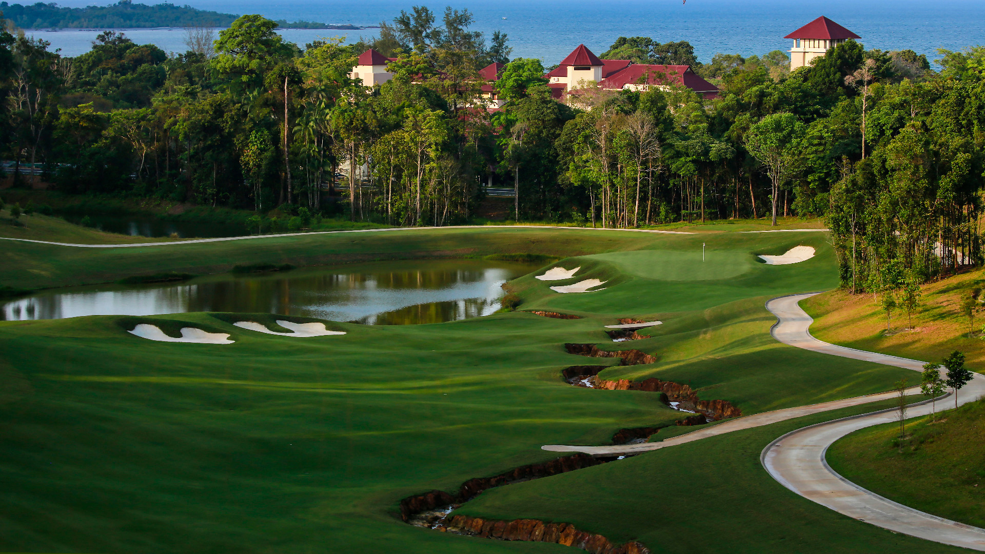 The Clubhouse peeks out from behind the trees at the Valley Club at The Els Club Malaysia - Desaru Coast